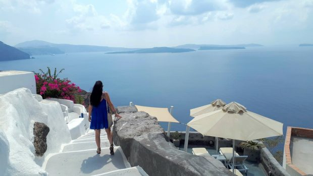 Back view of woman in blue sundress looking out over the sea