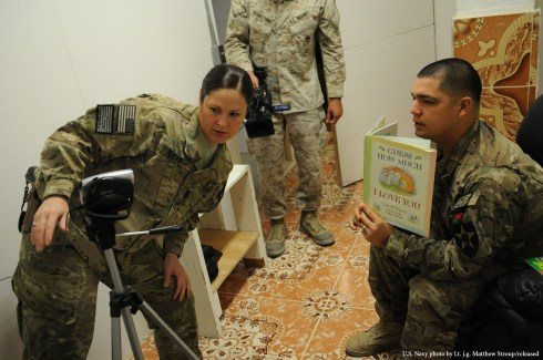U.S. Navy Hospital Corpsman 1st Class Jennifer Kleve, left, a medic with Provincial Reconstruction Team (PRT) Farah, helps set up a camera for U.S. Army Capt. Jacob Estrada, right, security force commander for the PRT, prior to his participation in a United Through Reading Read-a-thon on FOB Farah, Jan. 18.  Participants in the program were encouraged to read to children in their families or to students at Birch Elementary in Idaho, to promote childhood literacy.  United Through Reading is a non-profit organization that enables deployed service members to share their love and support with their children by reading books aloud on DVD.  PRT Farah's mission is to train, advise, and assist Afghan government leaders at the municipal, district, and provincial levels in Farah province Afghanistan.  Their civil military team is comprised of members of the U.S. Navy, U.S. Army, the U.S. Department of State and the U.S. Agency for International Development (USAID).  (U.S. Navy photo by Lt. j.g. Matthew Stroup/released)