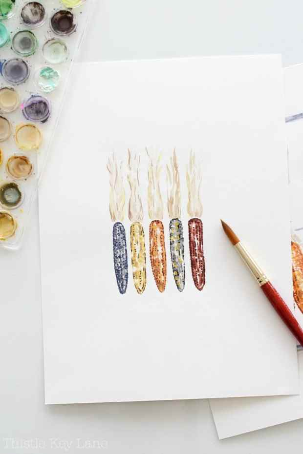 Watercolor paints to create a row of Indian corn.
