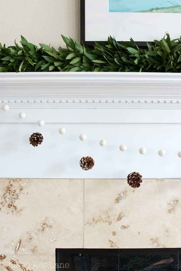 Simple decorations for the mantel with bay leaf garland and snowy pinecones.