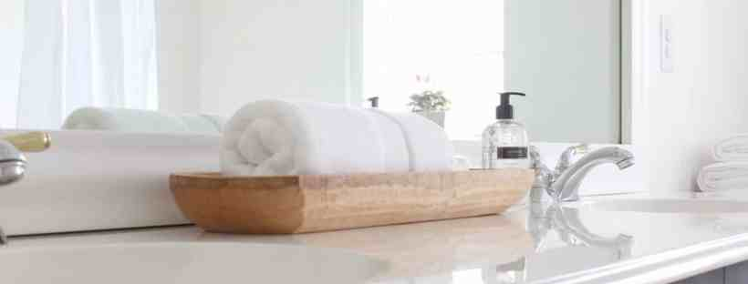 Wood dough bowl holds a towel and soaps.