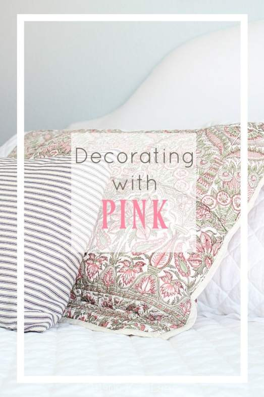 White bedding with ticking and pink patterned pillows.