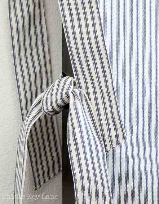 Ties from the same ticking fabric to hold slipcover in place.
