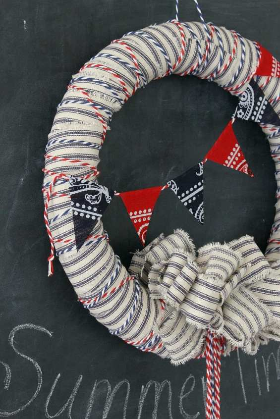 A summer wreath made from ticking fabric, colored string and scraps of bandanas.