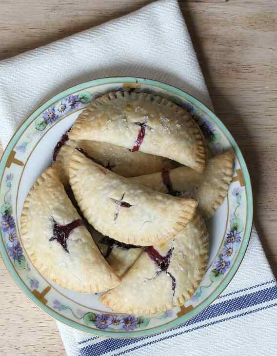 Blueberry hand pies on a hand painted china plate on a white tea towel.