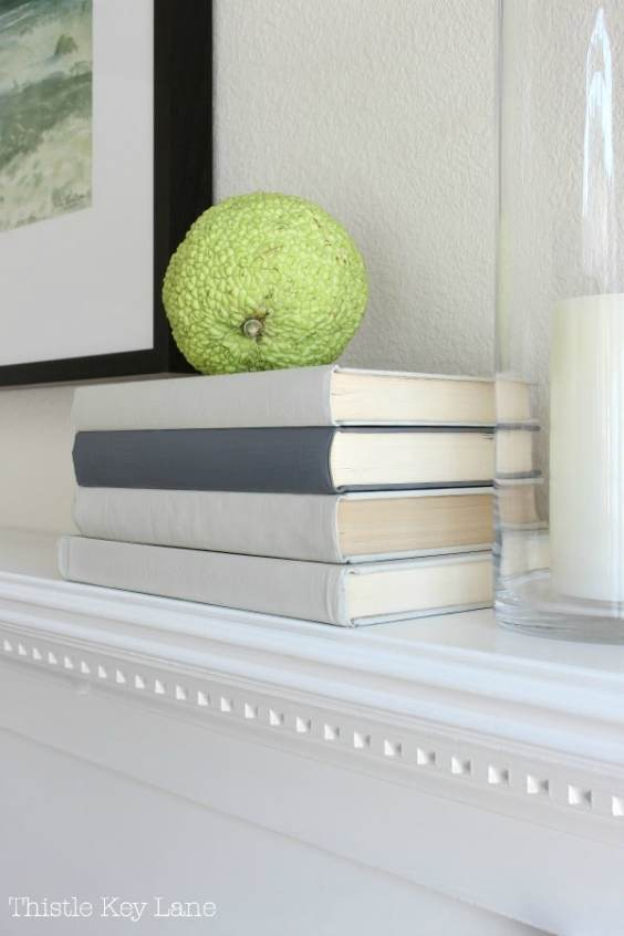 Painted books stacked on mantel.