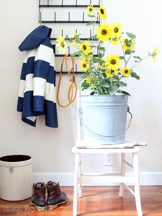 Entry with bucket of sunflowers, raincoat and boots.