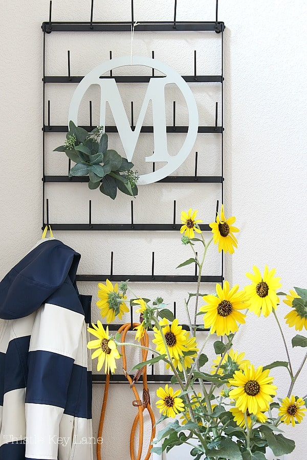 Coat rack decorated with an eucalyptus wreath and sunflowers.