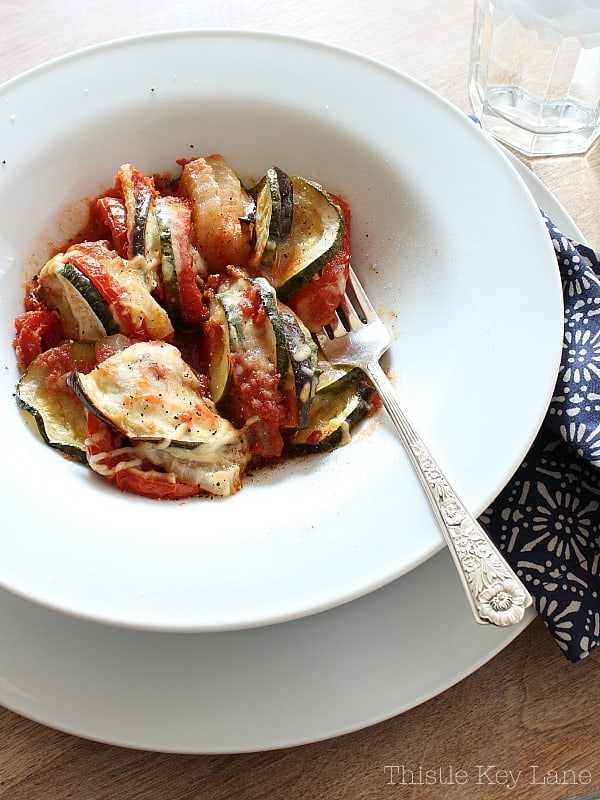 Baked eggplant, zucchini, tomatoes and onions in a white bowl. Ratatouille Recipe.
