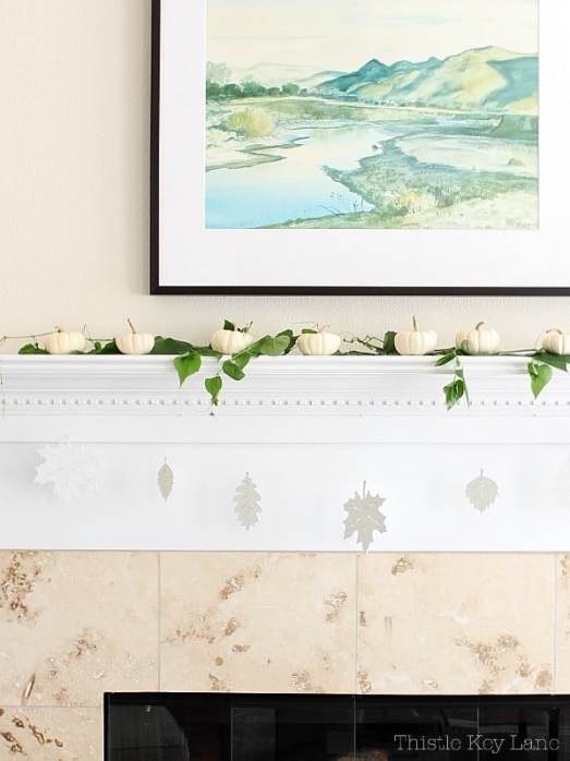 White mantel with pumpkins, vines and a leaf garland.