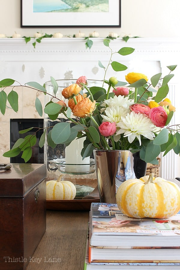 Decorate for fall with flowers and pumpkins.