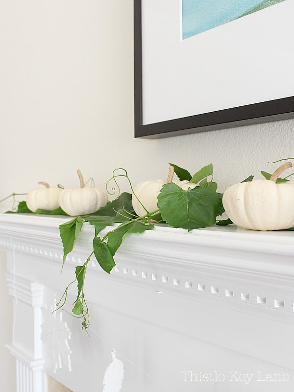White pumpkins lined up on the mantel with green vines.