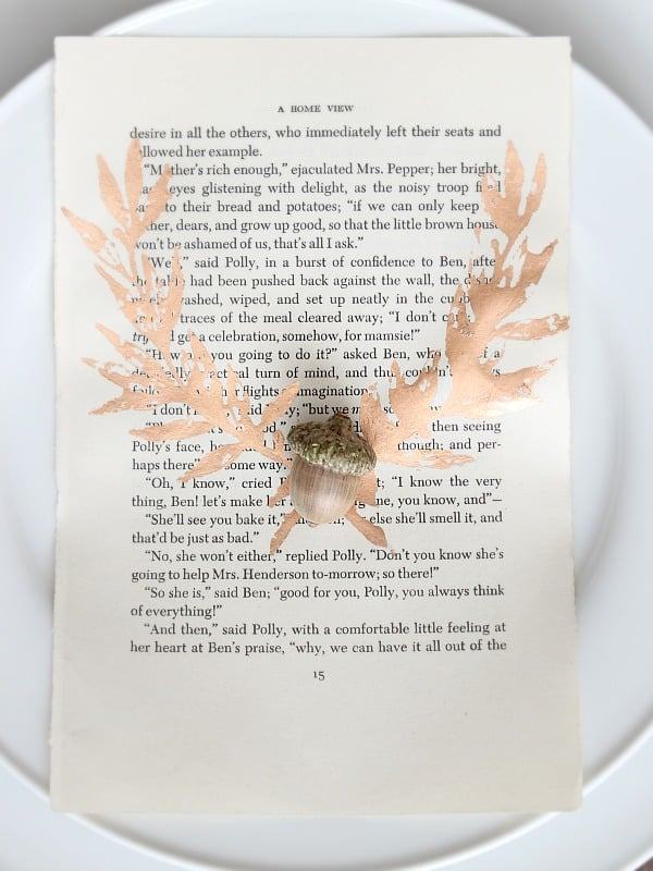 Book page on white plates with copper leaf laurel and an acorn.