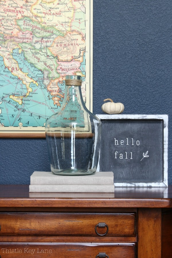 Hello fall chalk art on the entry table says welcome with books and glass bottle.