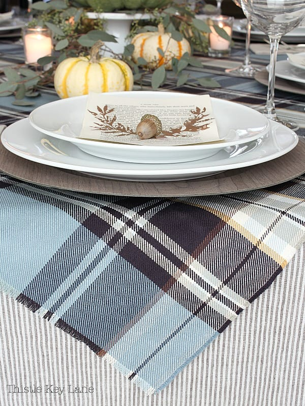 Plaid table cloth with white place setting and a copper laurel.