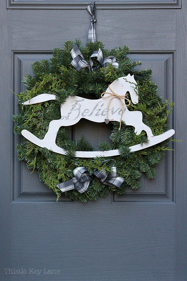 Green wreath with horse and plaid ribbon on dark gray door.