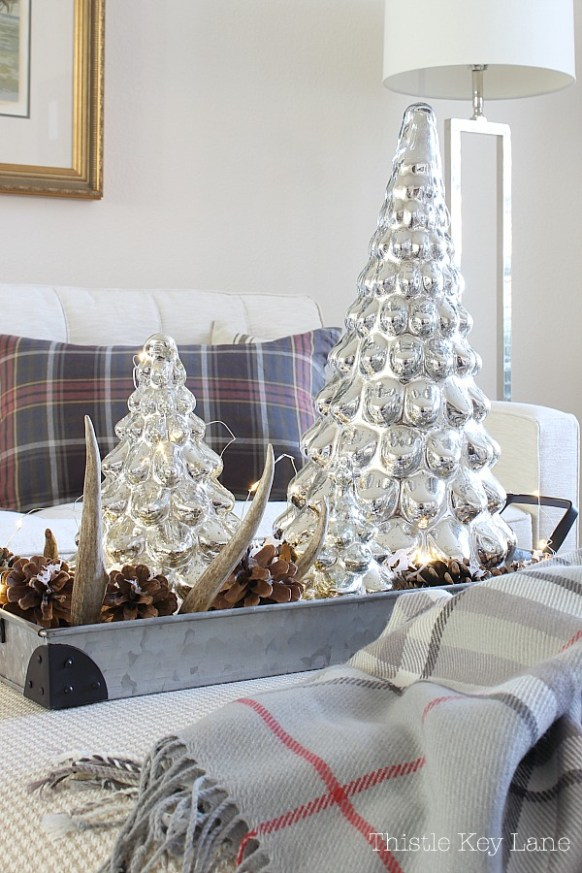Mercury glass trees, pinecones and fairy lights on a metal tray.