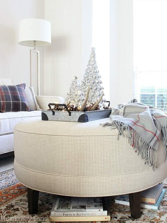 Cozy throw on an ottoman and a sparkly tray.