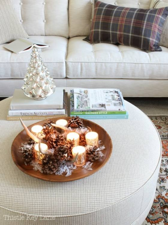 Cozy setting with candles and a tray sitting on an ottoman. Neutral colors.