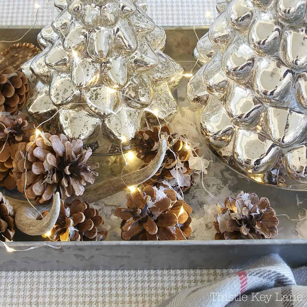 Fairy lights, mercury glass and pinecones.