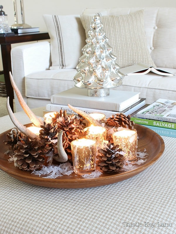 Wood tray with pinecones, an antler and votive candles.