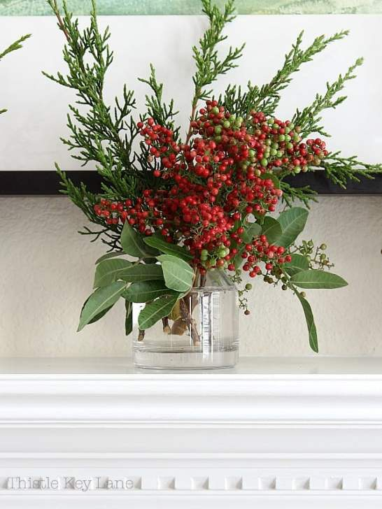 Pepper berries and cedar clippings in a clear vase.