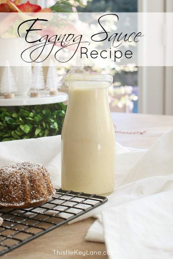 Milk bottle with eggnog sauce and mini cakes on wire rack.