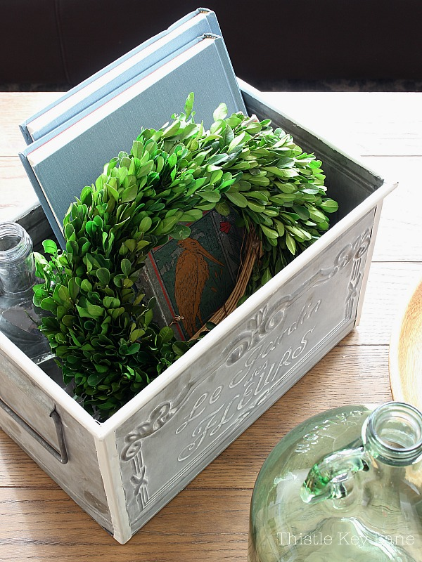 Metal box holding books and a wreath.