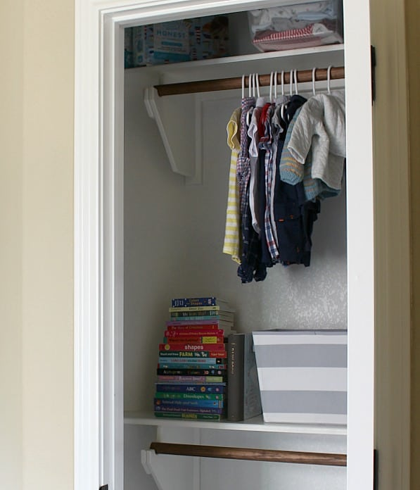 Baby clothes, book and storage bin in closet.