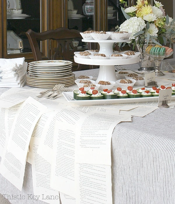 Book page table runner, stacked plates, cake stands and pretty food.