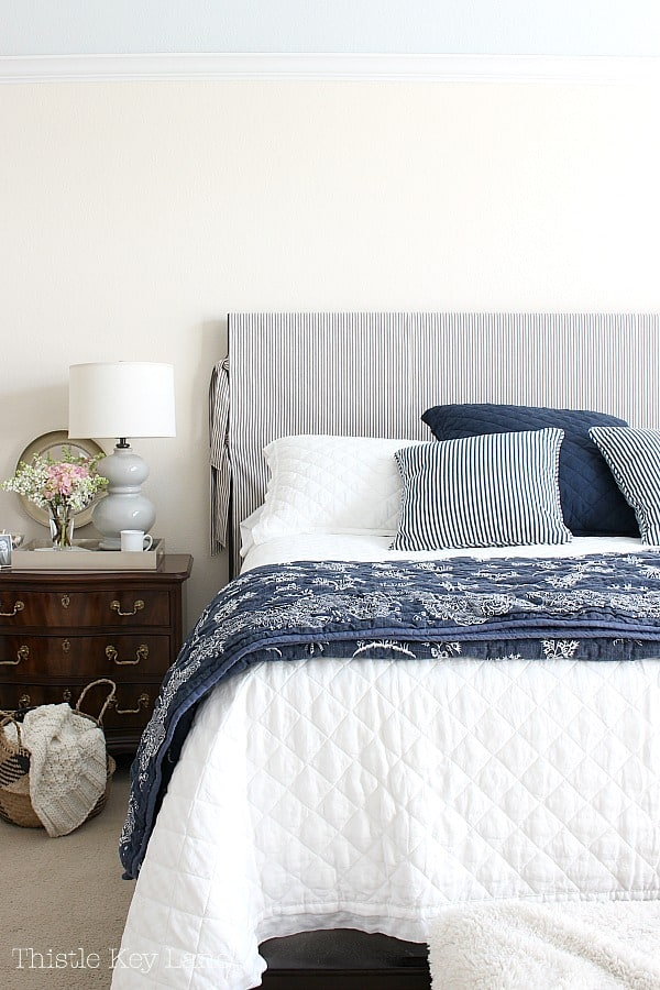 White and navy bed with side table and lamp.