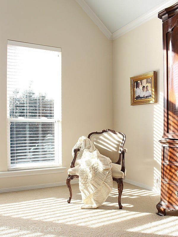 French arm chair draped with a blanket.
