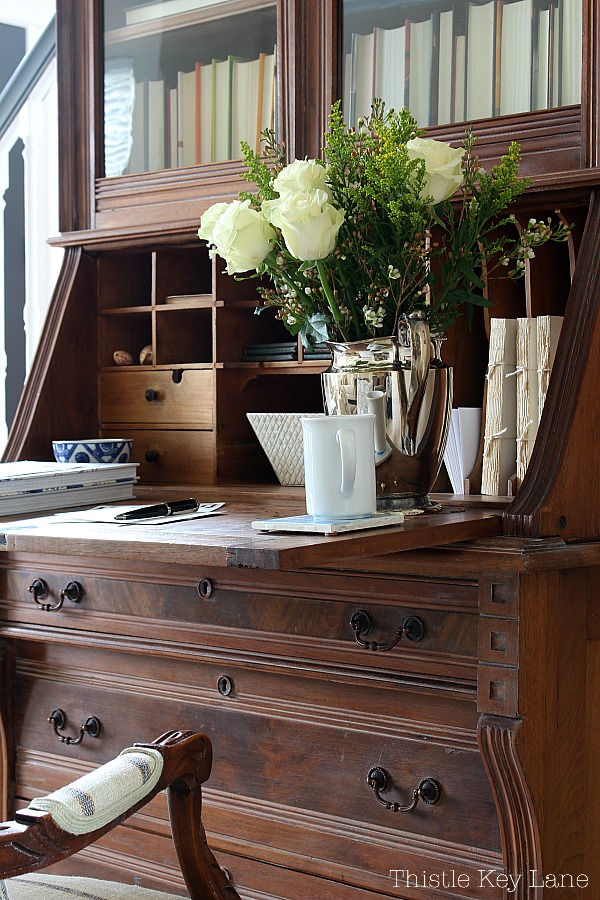 White roses in a silver pitcher on a vintage secretary desk.