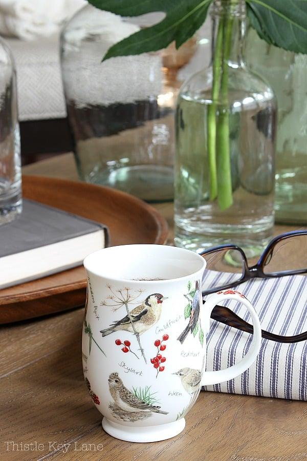 Tea cup with bird motifs, striped book, glass bottles.