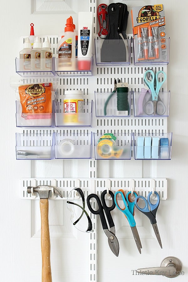 Storage rack on white door with craft supplies.