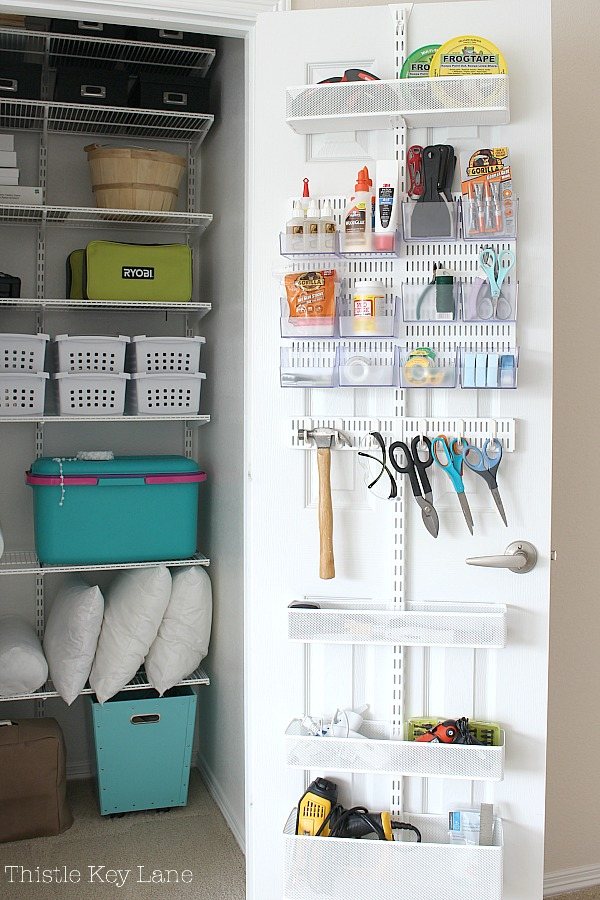Craft closet with storage shelves and door rack.
