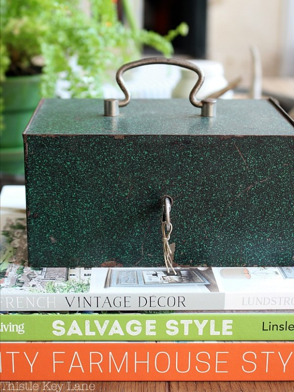 Vintage green metal log box and stacked books.