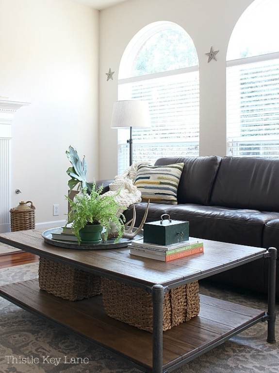 Big arch windows brown leather sofa and oversized coffee table.