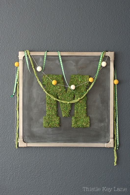 Chalkboard frames a moss letter M decorated with garlands.