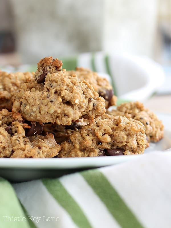 Oatmeal cookies on a white plate and a green striped kitchen towel.
