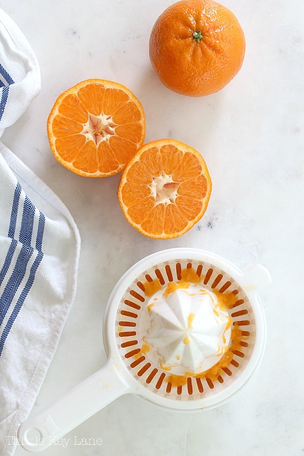 Oranges sliced on white marble next to a juicer.