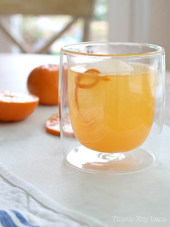 Orange cocktail in a clear glass with sliced oranges on white marble.