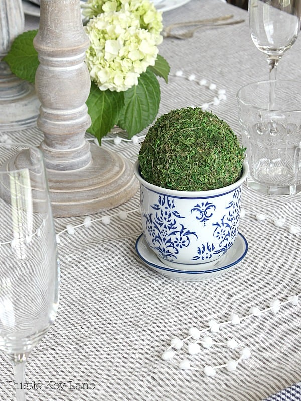 Mini moss topiary, string of pompoms on a neutral linen tablecloth.