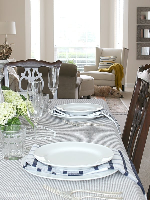 Table setting with white dishes, blue and white napkins and neutral tablecloth.