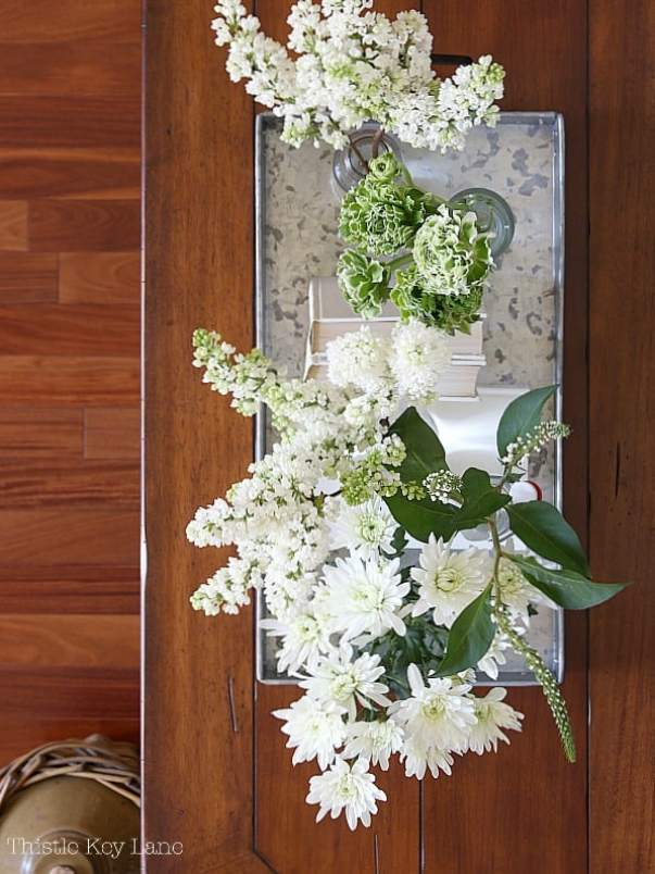 Top view of white flowers and vases on a tray.