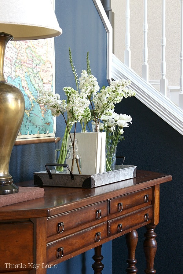 Entry table with flowers on a tray for a spring home tour.