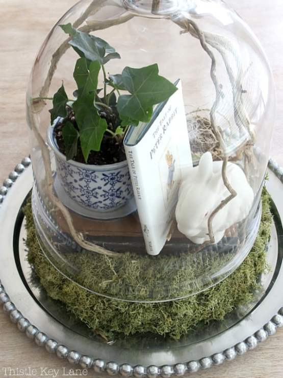 Top view of cloche with ivy, book, bunny and moss wreath.