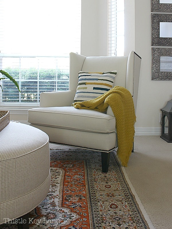 Cream wing back chair with stripe pillow and bright yellow throw in the spring home tour.