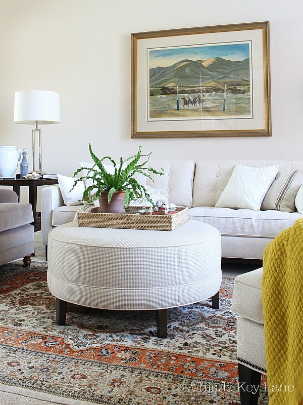 Large round ottoman in neutral room for a spring home tour.