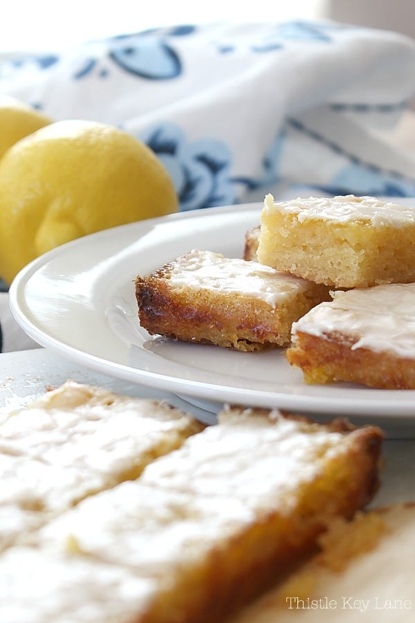 Cut lemon squares ready to serve on a white plate with lemons in the background.